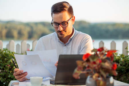 Serious young businessman working in a restaurant, preparing for important meeting. Looking over financial reports and sale charts, working on a laptop