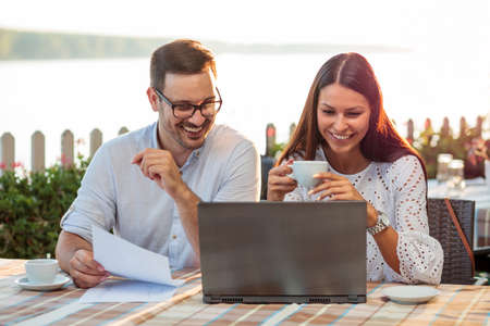Young male and female business people having a casual work meeting in a riverside cafe, looking at sale charts and contracts, working on a laptop and drinking coffee Standard-Bild