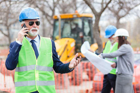 Serious senior architect or businessman talking on the phone while working on a construction site. Senior man and young woman looking at blueprints, blurred in the background.