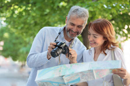 Two mid adult tourists visiting a foreign city. Walking through the park, woman is holding a map and man is showing pictures on a digital camera