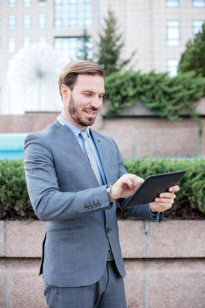 Young, handsome businessman working on a tablet in front of an office building. Work and stay connected anywhere concept