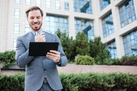 Happy young businessman working on a tablet in front of an office building. Work and stay connected anywhere concept Standard-Bild