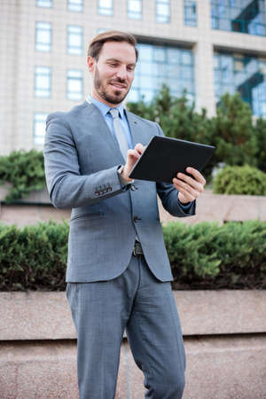 Young, handsome businessman working on a tablet in front of an office building. Low angle view. Work and stay connected anywhere concept Standard-Bild