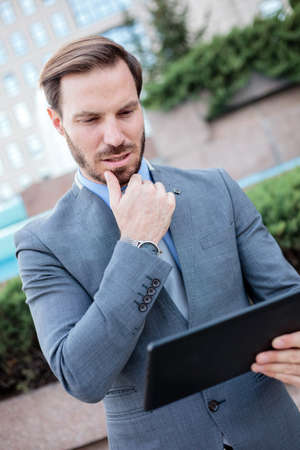 Successful young businessman working on a tablet in front of an office building. Holding hand on chin. Work and stay connected anywhere concept Standard-Bild