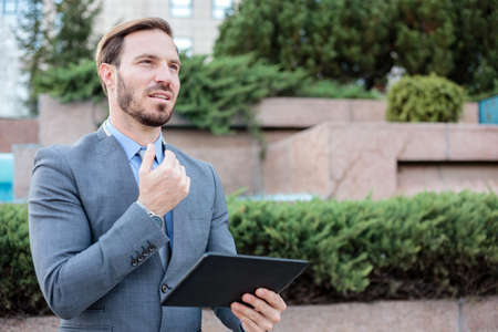 Successful young businessman working on a tablet in front of an office building. Holding hand on chin and looking into distance. Work and stay connected anywhere concept Standard-Bild
