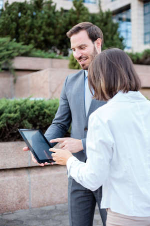 Handsome young male and female business people talking in front of an office building, having a meeting and discussing. Man is holding a tablet and pointing to display. Work anywhere concept. Standard-Bild