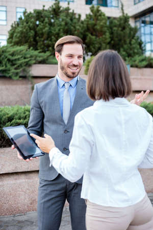 Handsome young male and female business people talking in front of an office building, having a meeting and discussing. Man is holding a tablet and looking at woman. Work anywhere concept.