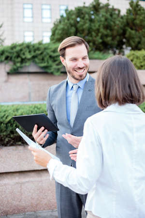 Successful young male and female business people talking in front of an office building, having a meeting and discussing. Man is holding a tablet and looking at woman. Work anywhere concept.