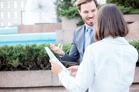Successful young male and female business people talking in front of an office building, having a meeting and discussing, looking at each other. Woman is holding paper reports. Work anywhere concept. Standard-Bild