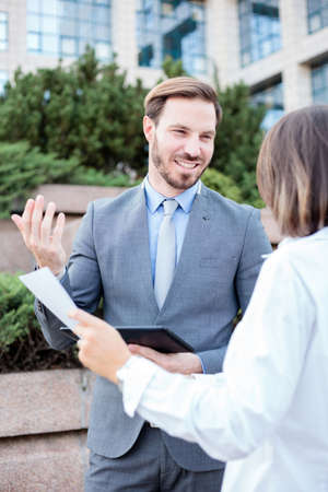 Young male and female business people talking in front of an office building, having a meeting and discussing, looking at each other. Woman is holding paper reports. Work anywhere concept. Standard-Bild