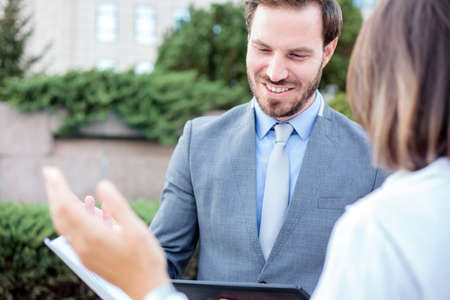Happy young male and female business people meeting in front of an office building, talking and discussing. Woman is showing graphs to a man. Work anywhere concept. Standard-Bild