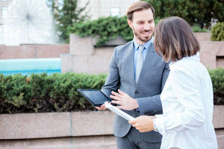 Happy young male and female business people talking in front of an office building, having a meeting and discussing, looking at paper charts and reports. Work anywhere concept. Standard-Bild