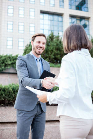 Young female and male businesspeople shaking hands after a successful meeting in front of an office building. Low angle view. Working in urban city streets Standard-Bild