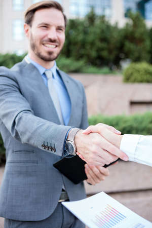Close up photo of young female and male businesspeople shaking hands after a successful meeting in front of an office building. Selective focus on hands in foreground. Work anywhere concept.