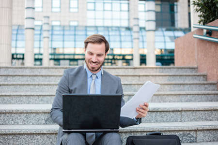 Handsome young businessman working on a laptop in front of an office building, checking paper reports. Low angle view. Work anywhere concept.