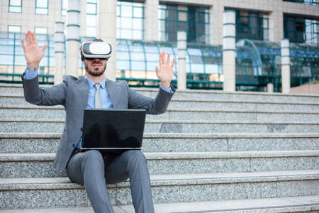 Handsome young businessman using VR goggles and making hand gestures, working on a laptop in front of an office building. Working with modern technologies concept Standard-Bild