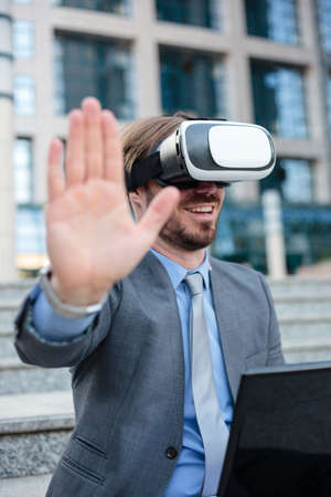 Close up of a young businessman using VR goggles in front of an office building. Selective focus concept, focus on head. Working with modern technologies concept Standard-Bild