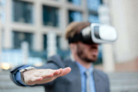 Close up of a young businessman using VR goggles in front of an office building, making hand gestures. Selective focus on his hand in foreground. Working with modern technologies concept