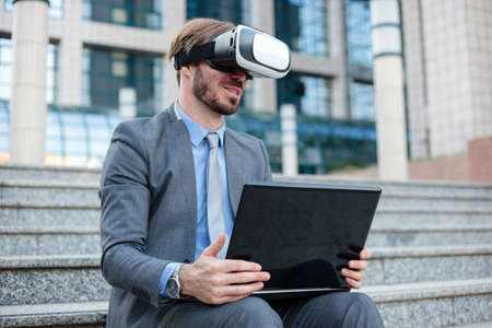 Successful young businessman using virtual reality simulator goggles and working on a laptop in front of an office building. Working with modern technologies concept Standard-Bild