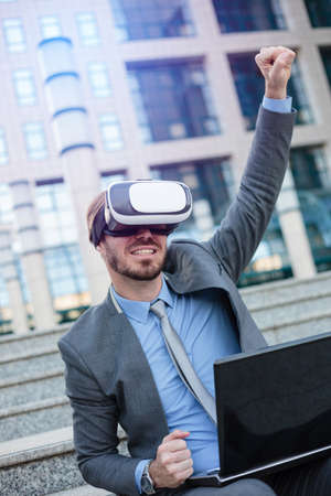 Happy young businessman using VR goggles, sitting in front of an office building with laptop. Celebrating success with fist high in the air. Working with modern technologies concept
