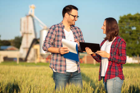 Two happy young male and female farmers or agronomists inspecting a wheat field before the harvest. Checking data on a tablet and clipboard. Organic farming and healthy food production.