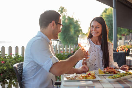 Beautiful happy young couple making a toast, celebrating anniversary or birthday in a restaurant. Husband and wife having romantic dinner in a restaurant by the river Standard-Bild