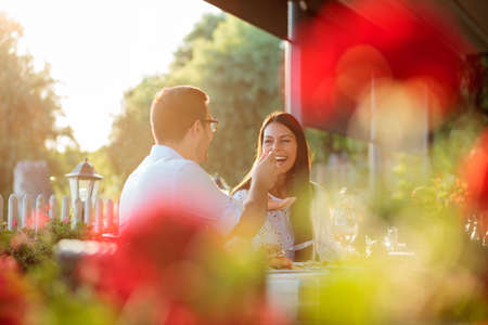 Smiling happy young couple enjoying dinner in outdoor restaurant, surrounded by green trees. Husband and wife celebrating birthday or anniversary, eating lunch in restaurant