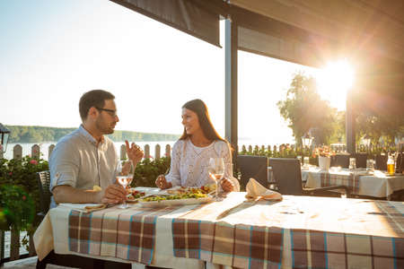 Happy young couple eating fish dinner and drinking wine in riverside restaurant. Husband and wife celebrating anniversary with lunch in restaurant. Sun setting behind the trees in the background Standard-Bild