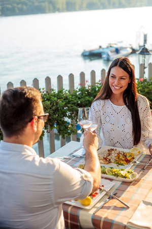 Romantic young couple making a toast, celebrating their anniversary or birthday in a restaurant by water. Husband and wife eating fish dinner in outdoor restaurant by the river