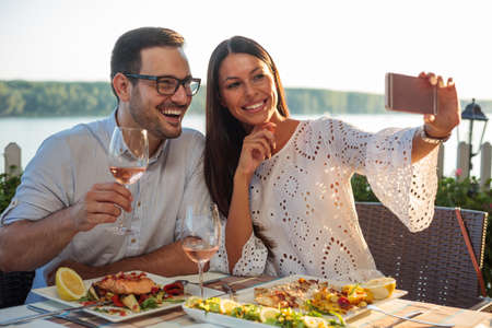 Smiling happy young couple posing for a selfie, eating dinner in a riverside restaurant. Husband and wife celebrating anniversary, having fish dinner in outdoor restaurant