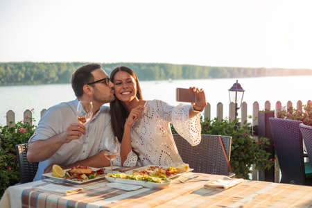 Smiling happy young couple posing for a selfie, eating dinner in a riverside restaurant. Man is kissing his girlfriend. Standard-Bild