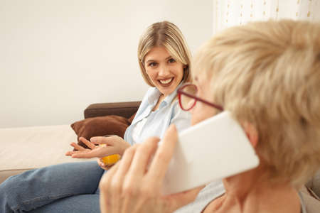 Young woman is curious and anticipating good news from her mother who is talking on the phone. Focus on daughter in background. Happy family moments at home