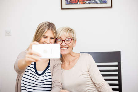 Senior mother and her daughter smiling and posing for a selfie while sitting by dinner table in bright room. Daughter holding phone. Happy family moments at home.