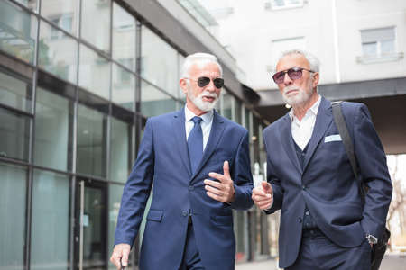 Two senior gray haired businessmen walking down the street, discussing and talking. Surrounded by modern glass office buildings