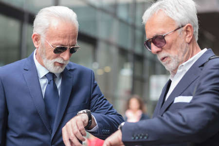 Two serious gray haired senior businessmen waiting for important meeting, checking time on wrist watch
