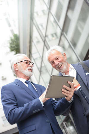Two smiling senior gray haired businessman looking at a tablet, standing in front of an office building during coffee break. Low angle view