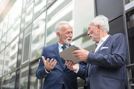 Two smiling senior gray haired businessman working a tablet and discussing. Standing in front of an office building. Low angle view