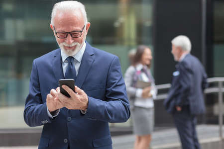 Successful happy senior gray haired businessman using smart phone, browsing internet or messaging. Two people talking in the background, blurred Stock Photo