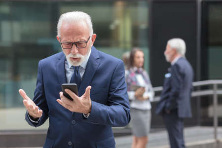 Worried senior businessman using smart phone in front of an office building. Messaging or browsing internet.