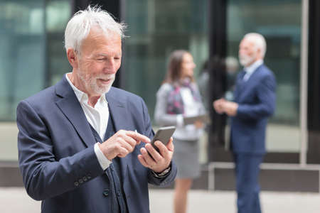 Happy senior gray haired businessman browsing internet or messaging on the smart phone, standing on the sidewalk in front of an office building.