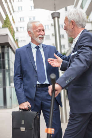 Two smiling senior businessmen meeting and talking on the sidewalk, surrounded by office buildings. Formal suits and tie, carrying a briefcase Standard-Bild