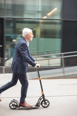 Serious senior gray-haired businessman commuting to work on a push scooter. Riding on a sidewalk in front of an office building
