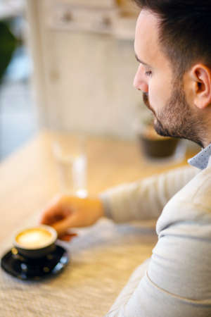 Young businessman drinking coffee while taking a break from a busy work day Standard-Bild