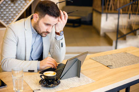Focused young businessman using a tablet while working in a modern coffee shop. Work anywhere concept.