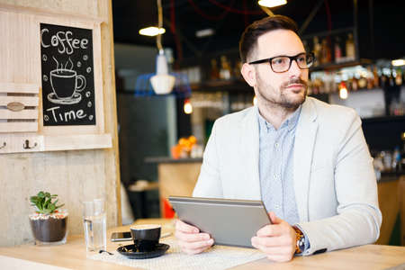 Young businessman using a tablet while working in a modern coffee shop. Work anywhere concept