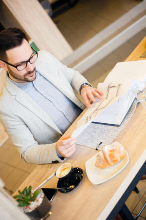 Young architect looking over building plans while working in a modern cafe. High angle view