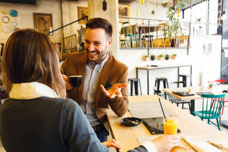 Young female and male business partners enjoying their coffee break during a busy work day. Work anywhere concept. Standard-Bild