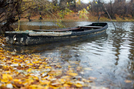 Old wooden rowing boat floating in water near shore on a rainy autumn day