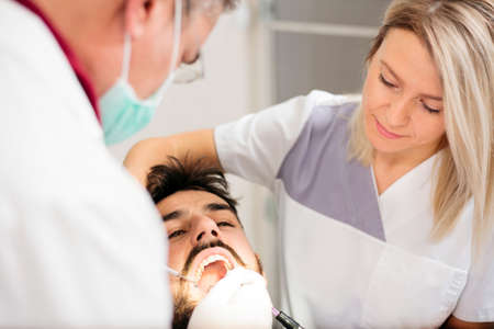Mixed team of dentists examining young male patient in a dental clinic. Health care and medicine concept. Standard-Bild