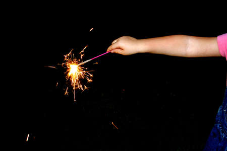 The arm of a youngster celebrating with sparks on black Stock Photo